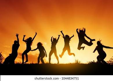 Group of people jumping against the sunset