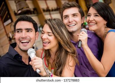 Group of people karaoke singing at a bar having fun