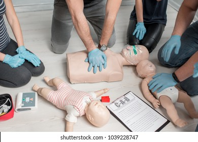 Group of people learning how to make first aid heart compressions with dummies during the training indoors. Close-up view on the hands and dummies