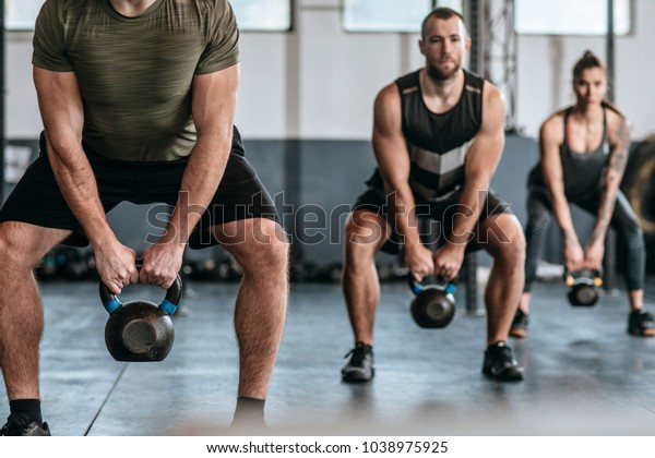 Group of people lifting weights at crossfit training at gym.