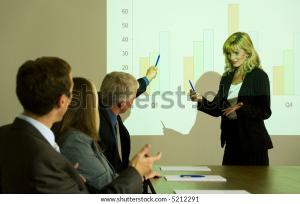 A group of people listening to a video presentation held by a blond woman, one attendant asking something