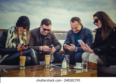 Group of people looking at a cell phone and laughing