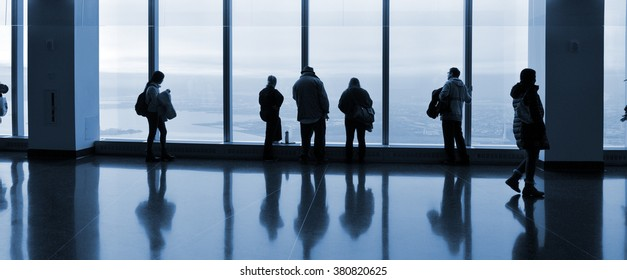 Group of people looking out at the window.