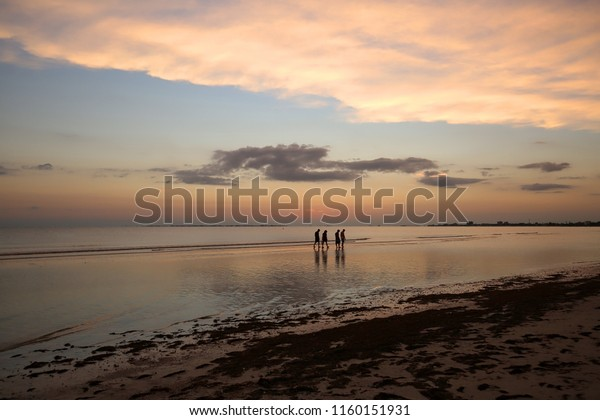 A group of people looking for sea shells as they enjoy the sunset on Fort Myers Beach, Florida.