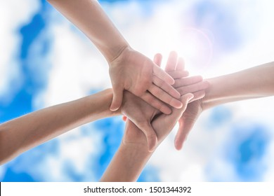 Group of people make hands together on blue sky background, team concept