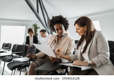 Group of people, making plans together, two females reading some documents.