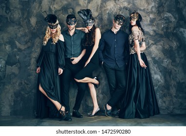Group of people in masquerade carnival mask posing in studio. Beautiful women and men wearing venetian mask. Fashion, party, friends concept