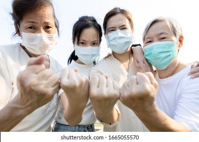 Group of people with medical mask to prevent infection from spreading of Covid-19,asian family raised a fists and prepare for the epidemic,fight the Coronavirus,overcoming a terrible crisis together