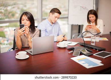 Group of people in a meeting room using their smartphones and ignoring work for a while