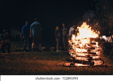 Group of people near camp fire with campfire song and campfire meals playing campfire games and eating camp fire grill, telling campfire stories near the fire with wood, flames in the nature at night.