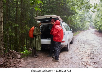 Group of people near an SUV car with open boot, ready to hike on trails