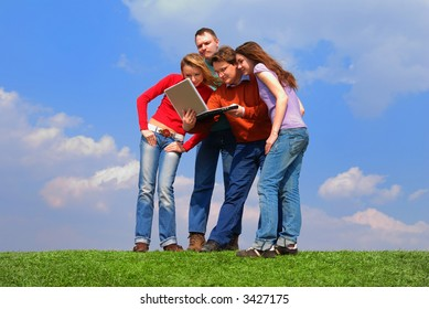 Group of people with notebook sitting on grass against sky