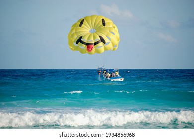A group of people on a boat in the bright blue ocean water preparing to parasail with a bright yellow parachute with a face on it.