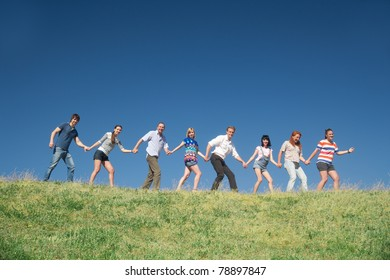 Group of people on hill hold hands together across blue sky