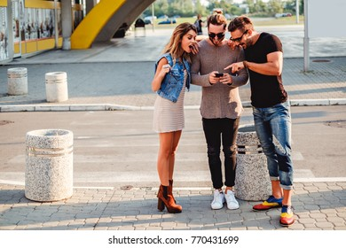 Group of people on the sidewalk looking at mobile phone and smile