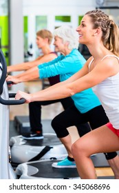 Group of people on vibrating plates in gym training