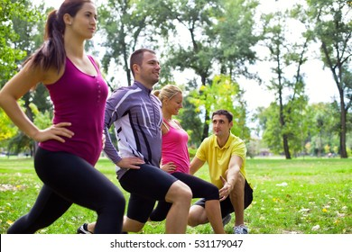 Group of people  out in the park doing squats. Trainer helps one of them