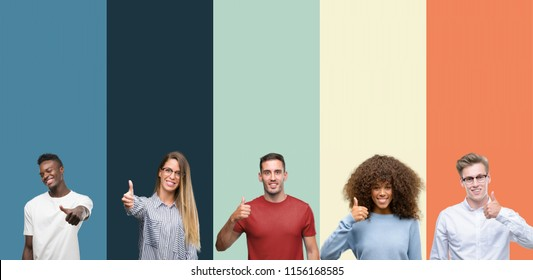 Group of people over vintage colors background doing happy thumbs up gesture with hand. Approving expression looking at the camera with showing success.