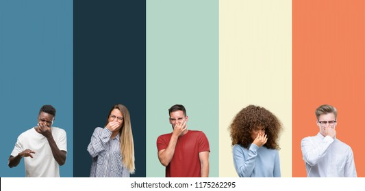 Group of people over vintage colors background smelling something stinky and disgusting, intolerable smell, holding breath with fingers on nose. Bad smells concept.