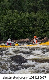 A group of people paddling the whitewater of the Noire River in Quebec, Canada.