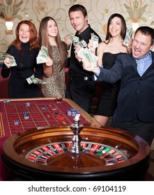 Group of people play roulette in casino
