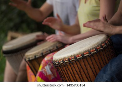 Group of people playing at djembe drums outdoor