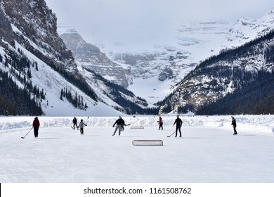 Group of people playing hockey on a frozen lake in Canada with glacier in the background