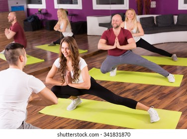 Group of people practicing yoga in a gym