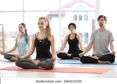 Group of people practicing yoga indoors