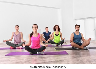 Group of people practicing yoga and meditating on mats