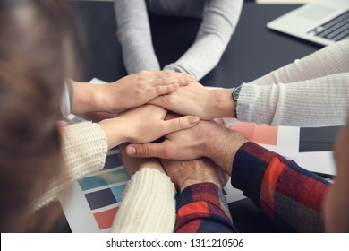 Group of people putting hands together as symbol of unity in office