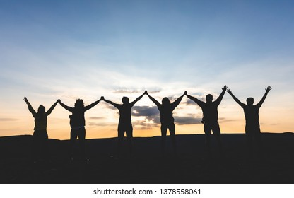 Group of people with raised arms holding hands and looking at sunset - Successful people and friends enjoying sunset together on top of a mountain - Achievement, celebration, friendship