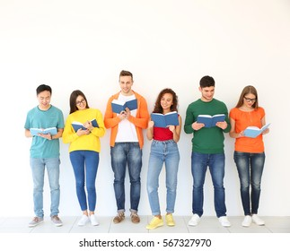 Group of people reading books while standing near light wall