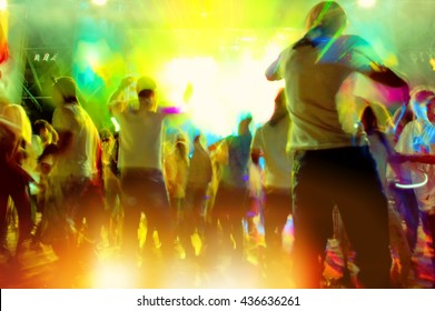 Group of People Relaxing and Having Fun at the Disco, Blurred Background. Concert Crowd. Rock Music.