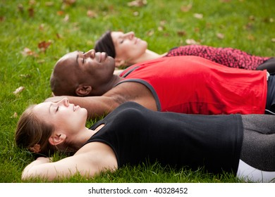 A group of people relaxing in a park after exercise