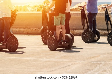 A group of people are riding on electric scooter hoverboard
