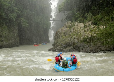 Group of people river rafting on Rio Pacuare in Costa Rica in the pouring Rain
