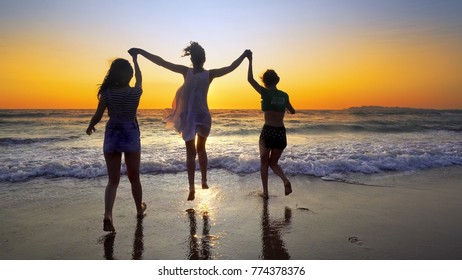 Group of people running on the beach in sunset holding for hands having fun jumping and spraying, cinematic steadicamshot
