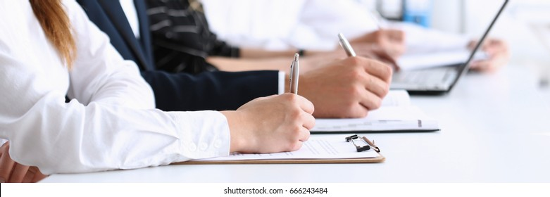 A group of people at the seminar listens attentively for good preparation and consolidation of knowledge received from the teacher make notes clipboards write the letter summary compiled correctly