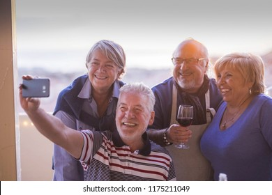 group of people senior adults caucasian having fun celebrating together outdoor at home in the terrace with rooftop view. taking picture selfie with phone technology smiling and laughing with joy.