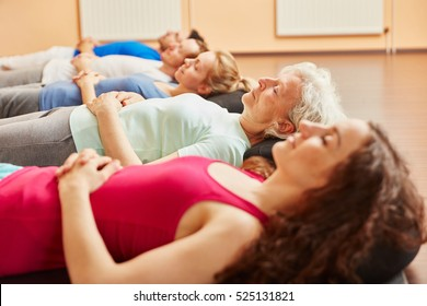 Group of people with senior relaxing  making breathing exercise at yoga class