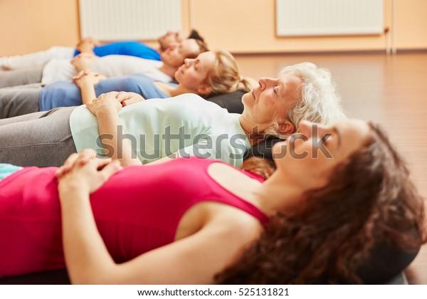 ヨガの授業でリラックスして呼吸運動をする人のグループ