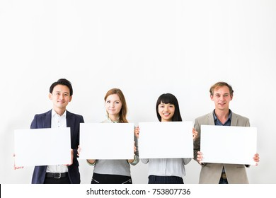 Group of people showing white boards.