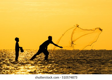 A group of people in silhouette spent quality time by casting a fishing net with orange sunset color at background.
