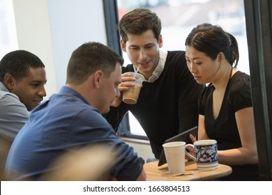 A group of people sitting around a table in a coffee shop. Looking at the screen of a digital tablet. Three men and a woman.