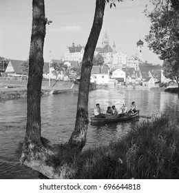 Group of people sitting in boat on river and city in background