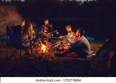 A group of people sitting by the bonfire next to the tent at night in the summer in autumn.