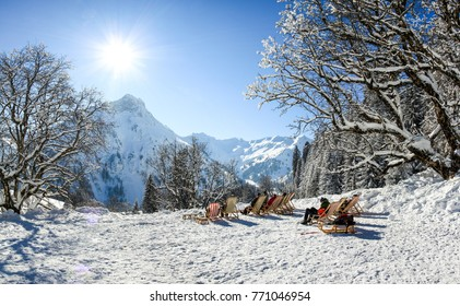 Group of people sitting with deck chairs in winter mountains. Sunbathing in snow. Germany, Bavaria, Allgau, Schwarzenberghuette.