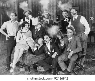 Group of people sitting in a living room smoking