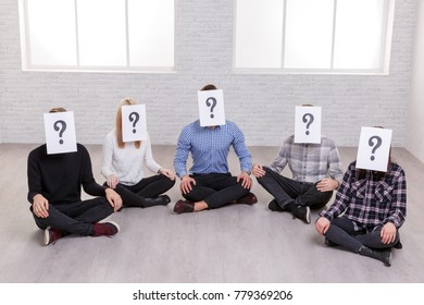 A group of people are sitting on the floor, on their faces are paper sheets with a question mark,.